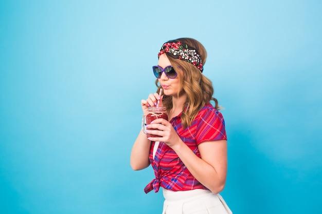 Jeune femme sexy hipster buvant un smoothie savoureux, tenue vintage, lunettes de soleil, portrait de style de vie en studio, dessert.