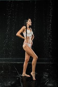 Jeune femme sexy en lingerie blanche. photo de studio d'eau.