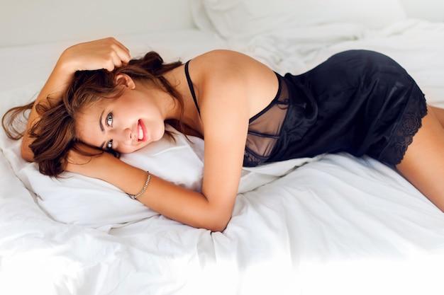 Jeune femme sexy en lingerie noire posant dans son lit