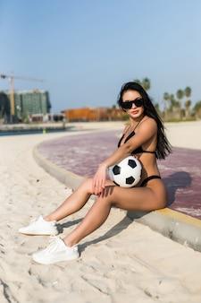 Jeune femme sexy en lunettes de soleil tenant un ballon de soccer sur la plage