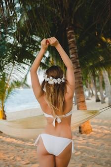 Jeune femme sexy en maillot de bain bikini blanc posant sur la plage tropicale, palmiers, hawaï, fleurs dans les cheveux, sensuel, corps mince, ensoleillé, vue de dos, profiter de vacances, voyager sur l'île