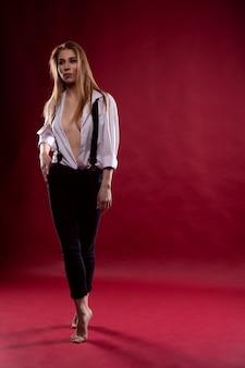Jeune femme sexy à la mode posant dans une chemise déboutonnée sur un fond rouge