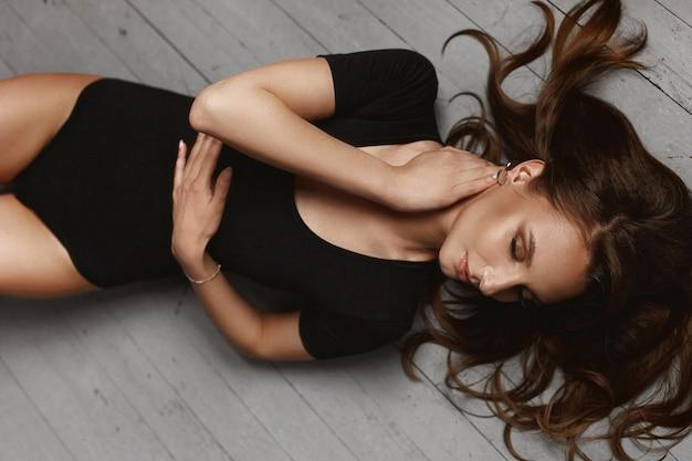 Jeune femme sexy modèle avec un corps parfait en body noir posant sur le plancher en bois clair à l'intérieur