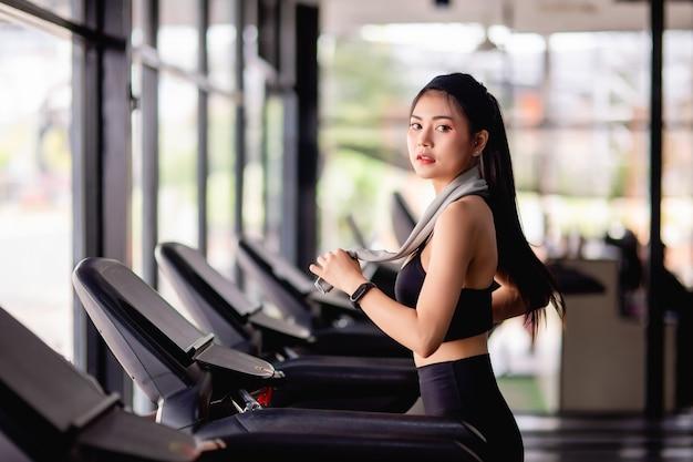 Jeune femme sexy portant des vêtements de sport, un tissu anti-transpiration et une montre intelligente marchant sur un tapis roulant se réchauffer avant de courir pour s'entraîner dans une salle de sport moderne, espace de copie