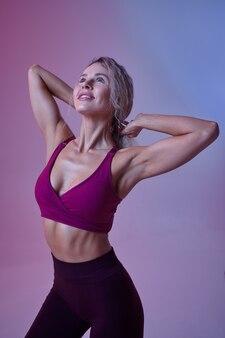 Jeune femme sexy avec des poses de corps mince en studio, fond néon