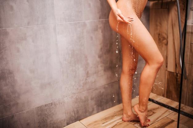 Jeune femme sexy séduisante dans la douche. corps mince bien construit. elle se tient debout sur un plancher en bois et se lave les mains du corps. l'eau tombe de la main.