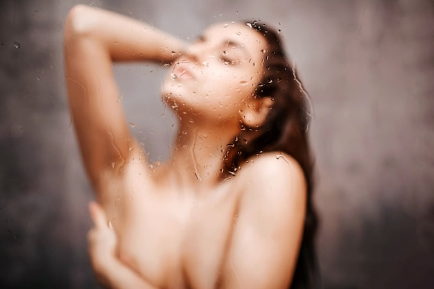 Jeune femme sexy séduisante dans la douche. sexy hot chic posant avec les yeux fermés. elle couvre la poitrine d'une main. photo floue.