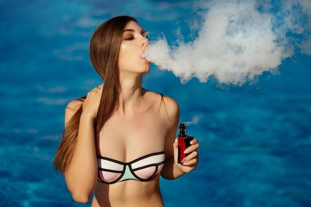 Jeune femme sexy vapote dans la piscine. un nuage de vapeur. femme chaude et sexy vapotant (fumant une e-cigarette) sur l'eau. vue rapprochée. concept de vapotage