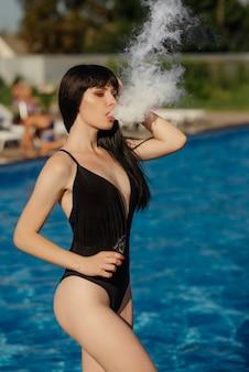 Jeune femme sexy vapote. un nuage de vapeur. femme chaude et sexy vapotant (fumant une e-cigarette) vue rapprochée. concept de vapotage