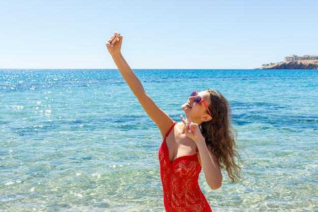 Jeune femme sexy vêtue d'un maillot de bain tendance avec appareil photo pour téléphone portable pour prendre selfie