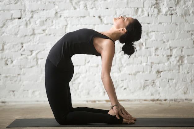 Jeune femme sexy yogi à ustrasana pose, grenouillère blanche