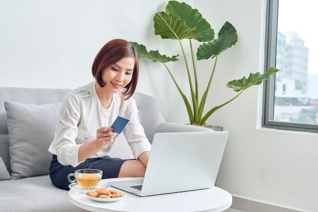 Jeune femme shopping en ligne avec carte de crédit et ordinateur portable à la maison
