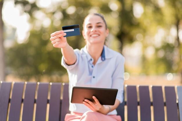 Jeune femme shopping en ligne dans le parc