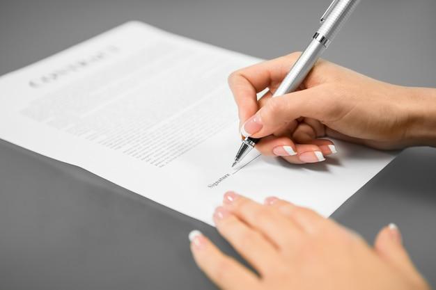 Une jeune femme signe un contrat de travail. réfléchissez et décidez. la dernière étape. route du succès.