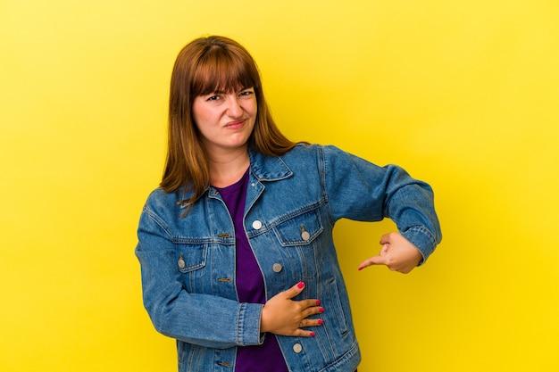 Jeune femme sinueuse caucasienne isolée sur fond jaune ayant une douleur au foie, des maux d'estomac.