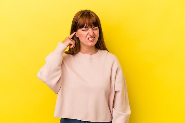 Jeune femme sinueuse caucasienne isolée sur fond jaune couvrant les oreilles avec les mains.