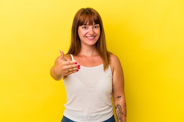 Jeune femme sinueuse caucasienne isolée sur fond jaune s'étendant la main à la caméra en geste de salutation.