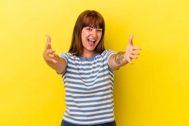 Jeune femme sinueuse caucasienne isolée sur fond jaune se sent confiante en donnant un câlin à la caméra.