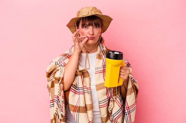 Jeune femme sinueuse caucasienne tenant une lanterne isolée sur fond rose avec les doigts sur les lèvres gardant un secret.
