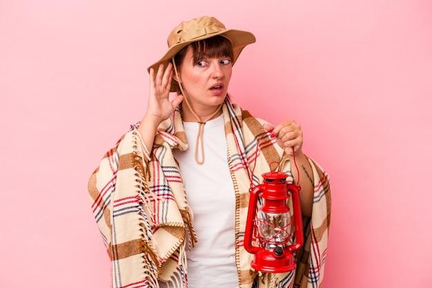 Jeune femme sinueuse caucasienne tenant une lanterne isolée sur fond rose essayant d'écouter un potin.