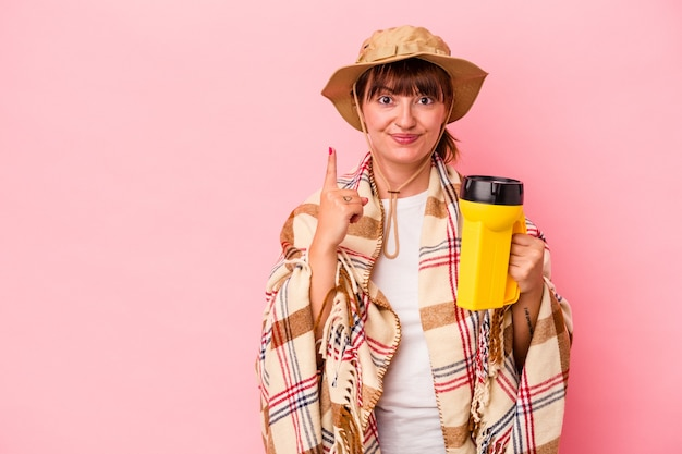 Jeune femme sinueuse caucasienne tenant une lanterne isolée sur fond rose montrant le numéro un avec le doigt.