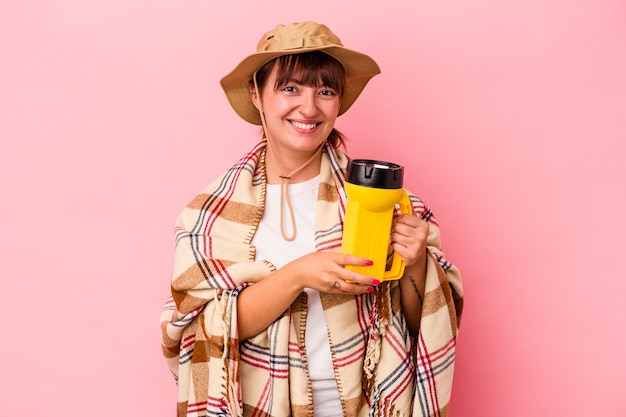 Jeune femme sinueuse caucasienne tenant une lanterne isolée sur fond rose en riant et en s'amusant.