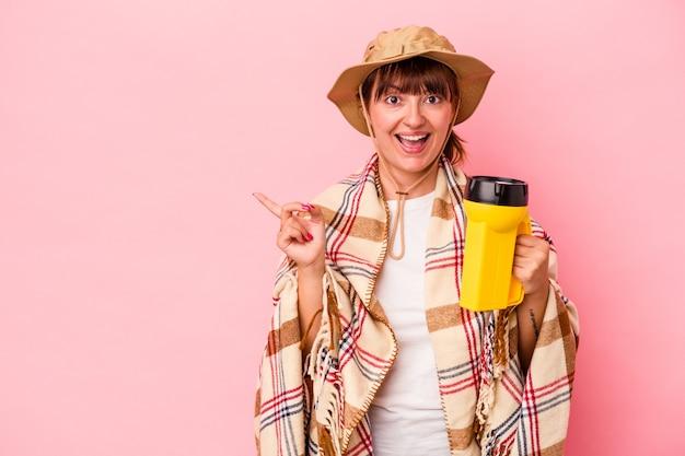 Jeune femme sinueuse caucasienne tenant une lanterne isolée sur fond rose souriante et pointant de côté, montrant quelque chose dans un espace vide.