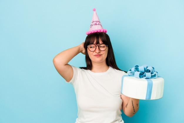 Jeune femme sinueuse célébrant son anniversaire isolée sur fond bleu touchant l'arrière de la tête, pensant et faisant un choix.