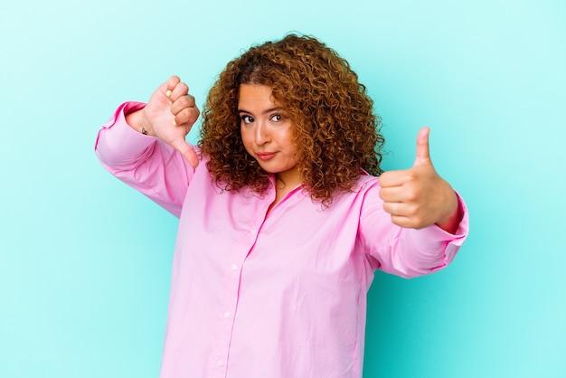 Jeune femme sinueuse latine isolée sur fond bleu montrant les pouces vers le haut et les pouces vers le bas, difficile de choisir le concept