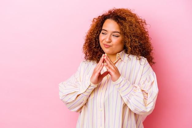 Jeune femme sinueuse latine isolée sur fond rose faisant plan à l'esprit, mettant en place une idée.