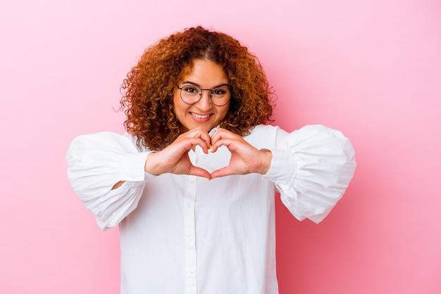 Jeune femme sinueuse latine isolée sur fond rose souriant et montrant une forme de coeur avec les mains.