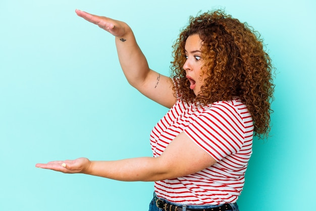 Jeune femme sinueuse latine isolée sur mur bleu choqué et étonné tenant un espace de copie entre les mains.