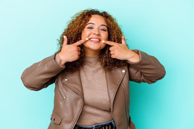 Jeune femme sinueuse latine isolée sur le mur bleu sourit, pointant du doigt la bouche.