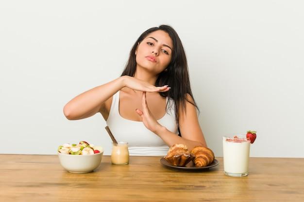 Jeune femme sinueuse prenant un petit-déjeuner montrant un geste de temporisation.