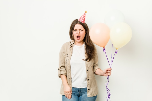 Jeune femme sinueuse de taille plus célébrant un anniversaire en criant très en colère et agressif.