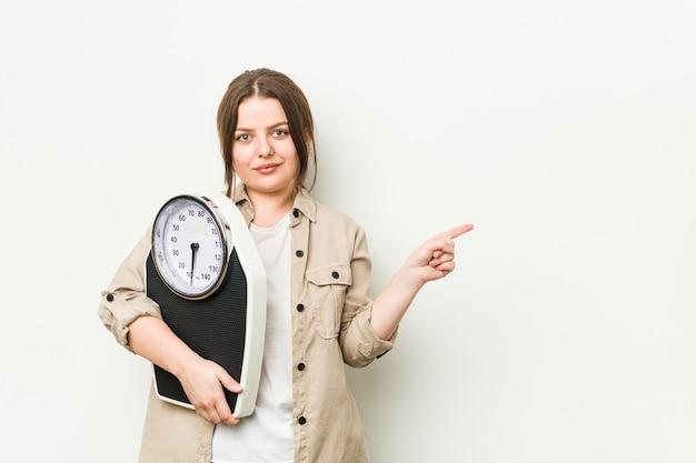Jeune femme sinueuse tenant une balance en souriant et pointant de côté, montrant quelque chose à l'espace vide.