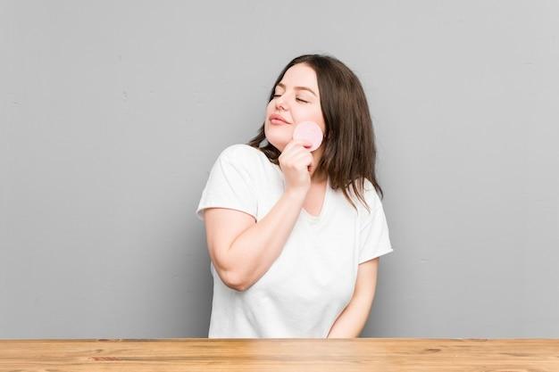 Jeune femme sinueuse tenant un disque facial isolé sur un mur gris