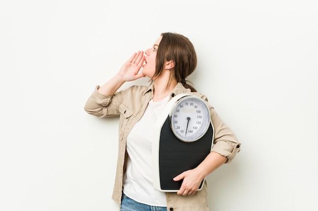 Jeune femme sinueuse tenant une échelle criant et tenant la paume près de la bouche ouverte.