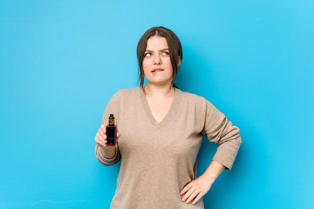 Jeune femme sinueuse tenant un vaporisateur confuse, se sent douteuse et incertaine.