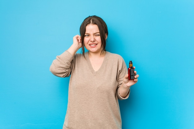 Jeune femme sinueuse tenant un vaporisateur couvrant les oreilles avec les mains.