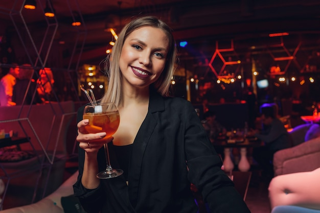 Jeune femme en sirotant une boisson sucrée rouge au bar