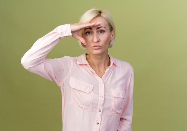 Jeune femme slave blonde regardant à distance avec la main isolée sur vert olive