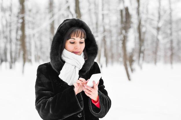 Jeune femme avec smartphone et flocons de neige de paysage d'hiver sur le fond.