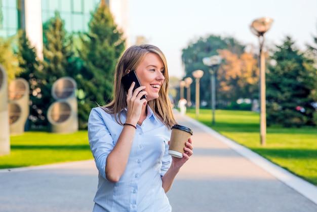 Jeune femme avec un smartphone marchant sur la rue, au centre-ville. en arrière-plan, la rue floue, en face