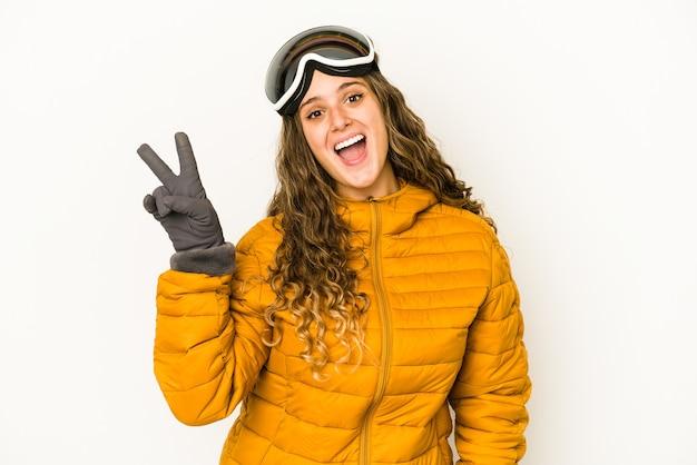 Jeune femme de snowboarder caucasien joyeux et insouciant montrant un symbole de paix avec les doigts.