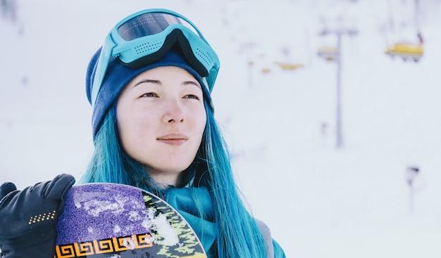Jeune femme snowboarder sur station de ski