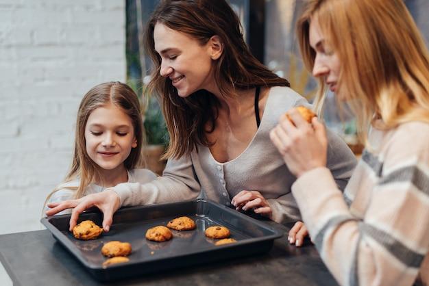Une jeune femme et son amie sont curieuses des cookies que sa fille a faits.