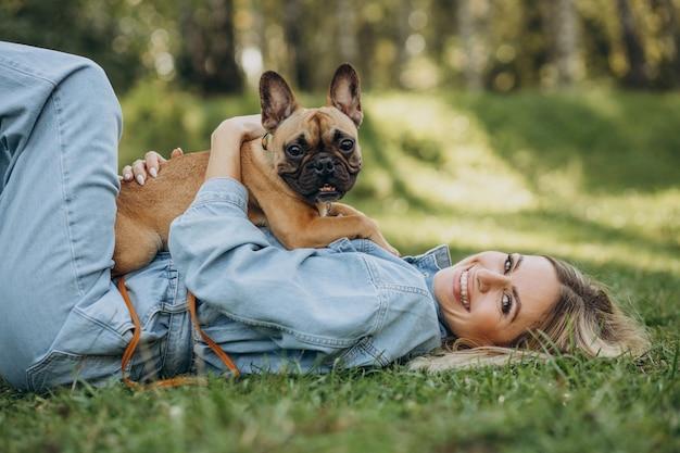 Jeune femme avec son animal de compagnie bouledogue français dans le parc