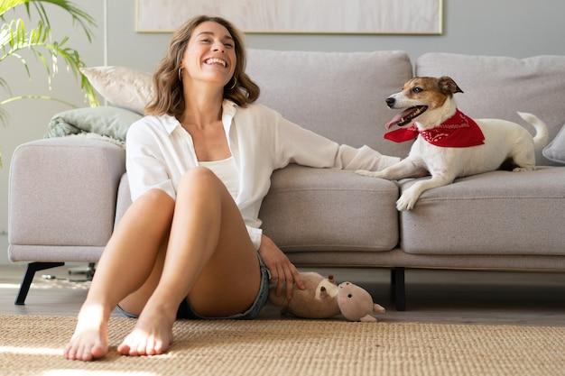 Jeune femme et son chien sur le canapé à la maison. animal de compagnie adorable. animal domestique
