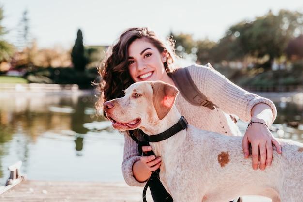 Jeune femme et son chien à l'extérieur dans un parc avec un lac. journée ensoleillée, saison d'automne